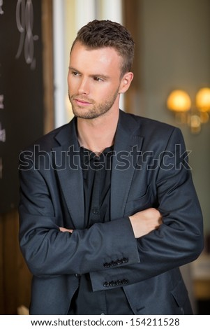 Thoughtful young businessman standing arms crossed in coffeeshop - stock photo
