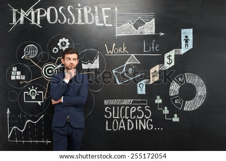 Thoughtful young businessman standing on dark chalkboard background. Colorful symbols and graphs painted on it. Concept for successful project