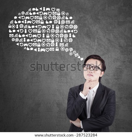 Thoughtful young businessman wearing formal suit and imagine web icons - stock photo