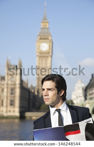 Thoughtful young businessman with book against Big Ben clock tower, London, UK - stock photo