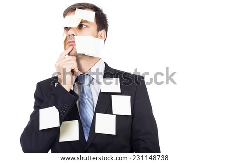Thoughtful young  businessman with post-it notes on his face and body over white background - stock photo