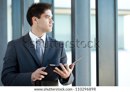 thoughtful young businessman with tablet computer - stock photo