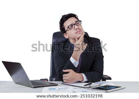 Thoughtful young businessperson in business suit working on desk while thinking a plan, isolated on white - stock photo