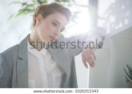 thoughtful young businesswoman leaning on bokshelves at office