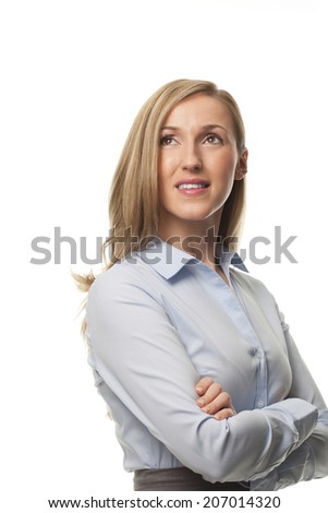 Thoughtful young businesswoman standing with folded arms looking up into the air with a pensive expression lost in a reverie, isolated on white - stock photo