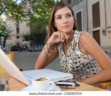 Thoughtful young businesswoman using a laptop computer and other technology while sitting down at a coffee shop terrace table, outdoors. - stock photo