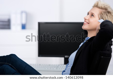 Thoughtful young businesswoman with hands behind head resting at office desk - stock photo
