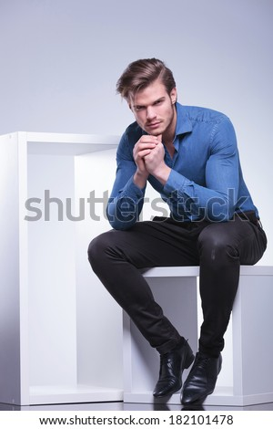 thoughtful young casual man is sitting and looks at the camera with head on his hands - stock photo