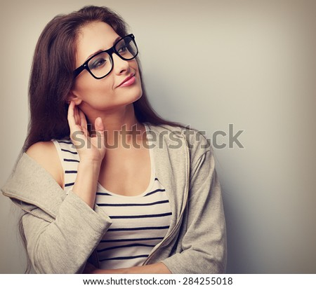Thoughtful young casual woman looking with hand near face. Closeup vintage portrait - stock photo