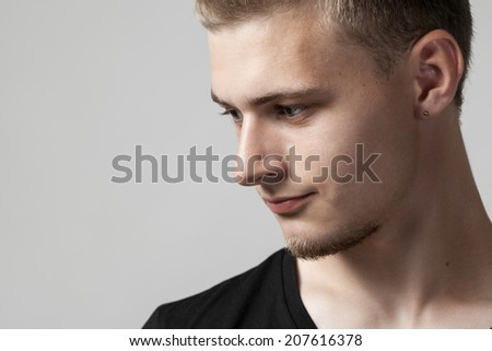 thoughtful young caucasian man isolated on gray background