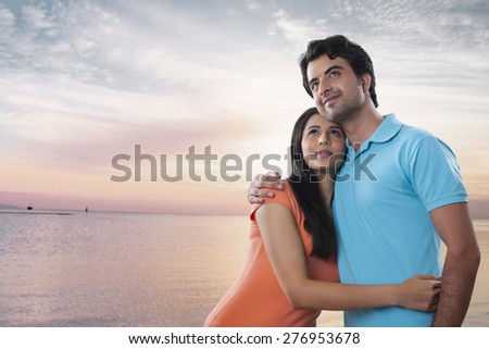 Thoughtful young couple embracing at beach - stock photo