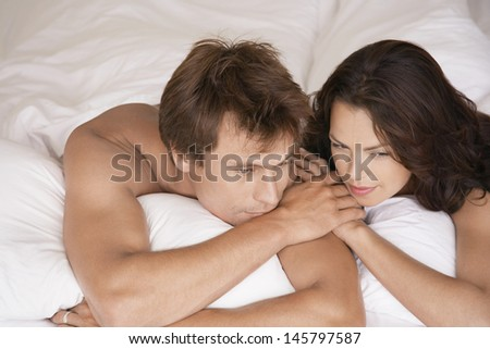 Thoughtful young couple lying in bed looking away