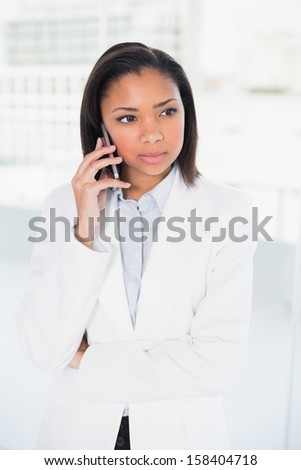 Thoughtful young dark haired businesswoman making a phone call in bright office - stock photo