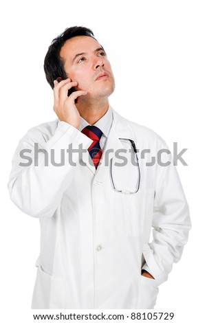 Thoughtful young doctor talking on the phone on white background - stock photo