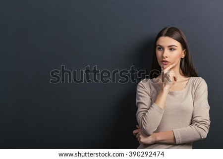 Thoughtful young female student is looking away, keeping hand on chin and thinking, standing against blackboard - stock photo