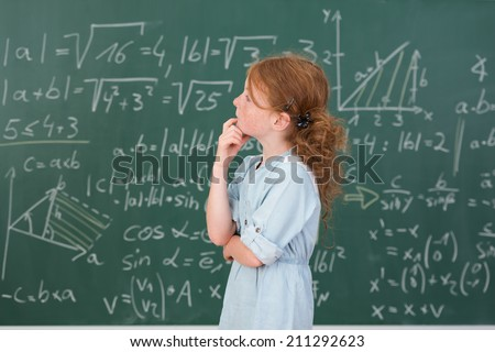 Thoughtful young girl in mathematics class standing sideways looking up at a blackboard covered in equations with her hand to her chin as she seeks an answer to a problem