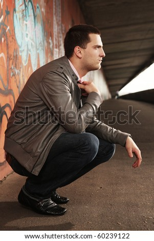 thoughtful young guy sitting in tunnel - stock photo