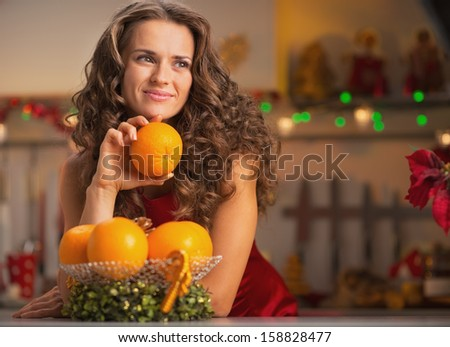 Thoughtful young housewife with orange in christmas decorated kitchen