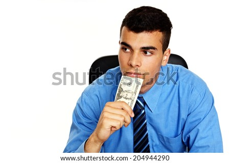 Thoughtful young man in blue shirt with money - stock photo