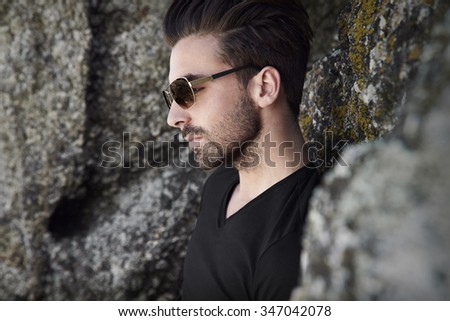 Thoughtful young man in sunglasses by rocks - stock photo