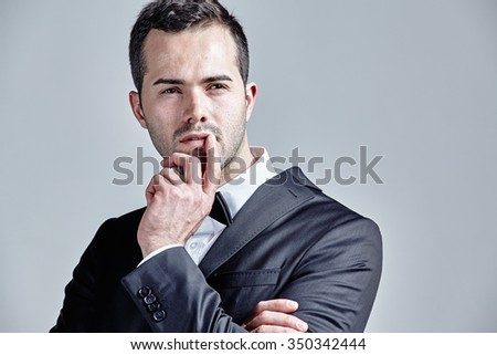 Thoughtful young man pointing finger over his lips isolated over grey - stock photo