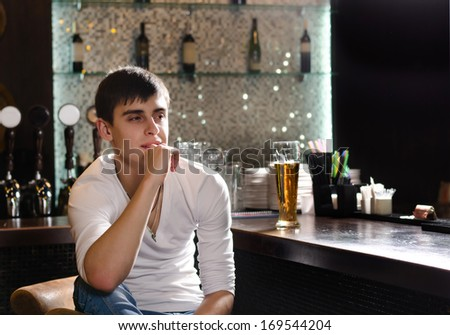 Thoughtful young man sitting thinking in a bar staring into the distance in contemplation - stock photo