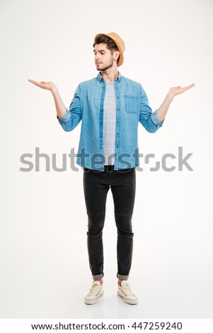 Thoughtful young man standing and holding copyspace on both palms over white background - stock photo