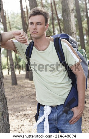Thoughtful young man with backpack in woods
