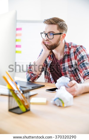 Thoughtful young man with beard in plaid shirt working and crumpling paper in the office - stock photo