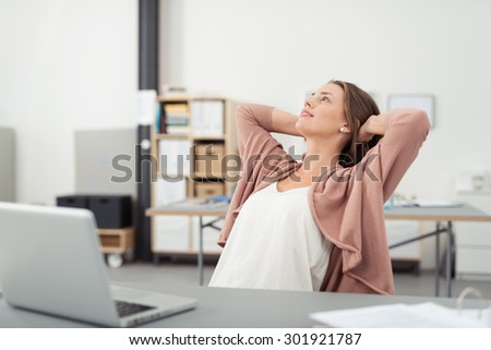 Thoughtful Young Office Girl Relaxing at her Workplace While Leaning her Back on a Chair and Looking Up with Both Hands Holding Behind her Head