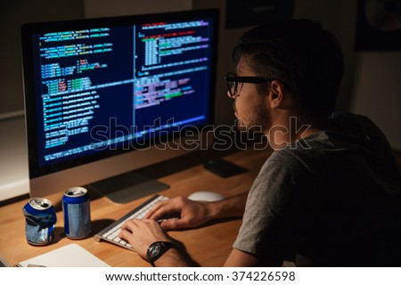 Thoughtful young programmer coding on computer in the evening at home - stock photo