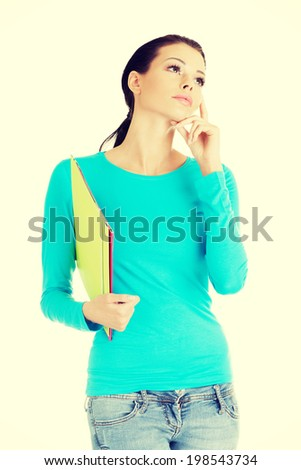 Thoughtful young student woman with notebook looking up