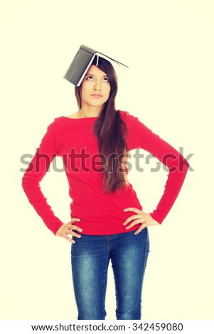 Thoughtful young student woman with notebook on head. - stock photo