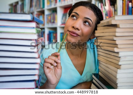 Thoughtful young woman amidst books in library