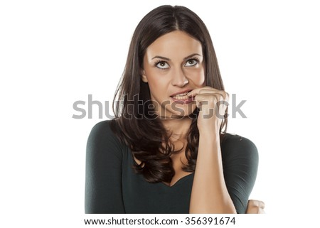 thoughtful young woman biting his fingernails  - stock photo
