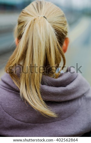 thoughtful young woman from behind - stock photo