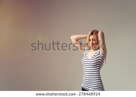 Thoughtful Young Woman in Casual Striped Shirt Holding Back her Long Blond Hair with Eyes Closed Against Brown Background. - stock photo