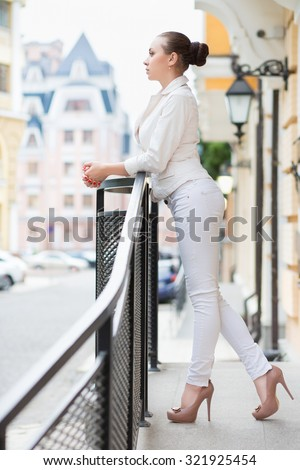 Thoughtful young woman in white pants and jacket posing outdoors - stock photo