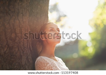 Thoughtful young woman lean against tree - stock photo