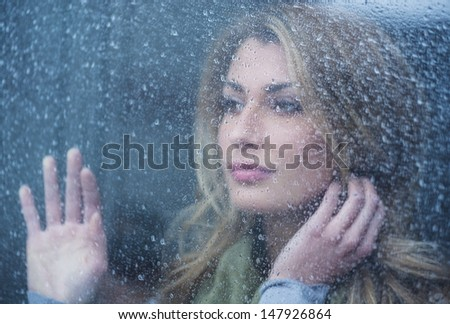 Thoughtful young woman looking through glass window with raindrops - stock photo