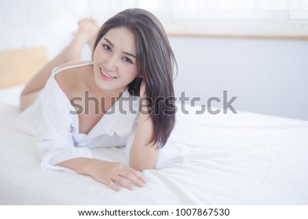 Thoughtful Young Woman Lying On Bed At Home