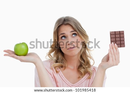 Thoughtful young woman making a decision against a white background - stock photo