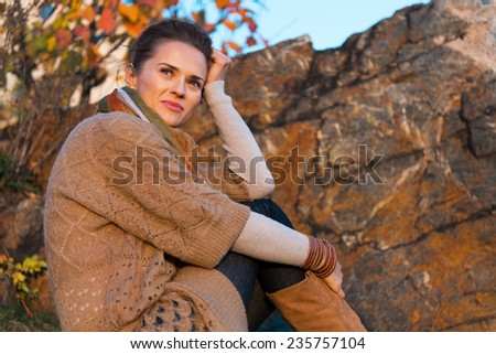 Thoughtful young woman sitting in autumn outdoors in evening