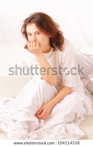 Thoughtful young woman sitting in bed - stock photo