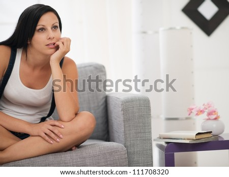 Thoughtful young woman sitting on sofa in modern living room - stock photo