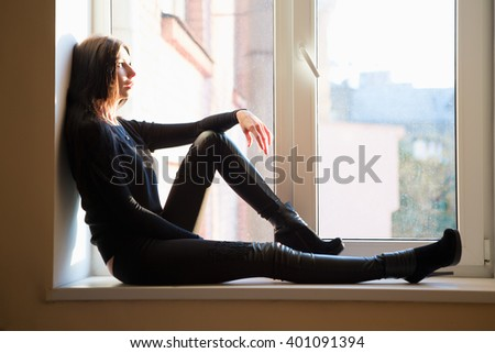 Thoughtful young woman wearing black clothes posing on the windowsill - stock photo