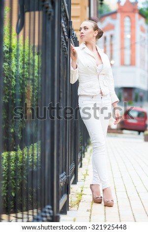 Thoughtful young woman wearing white pants and jacket posing near metal fence - stock photo