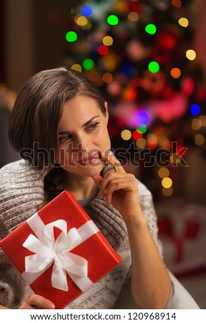 Thoughtful young woman with Christmas present box - stock photo