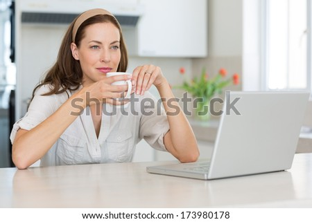 Thoughtful young woman with coffee cup and laptop in the kitchen at home