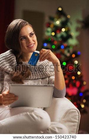 Thoughtful young woman with credit card and tablet pc near christmas tree - stock photo